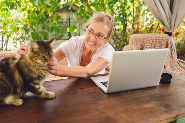 Ältere glückliche ältere frau mit hauskatze verwenden drahtlose kopfhörer, die online mit laptop im freien im garten arbeiten. heimarbeit
