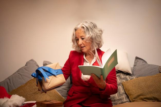 Ältere glückliche frau, die buch und geschenk hält