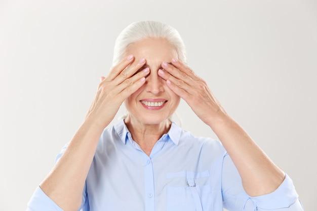 Ältere grauhaarige frau, die ihre augen mit beiden händen bedeckt