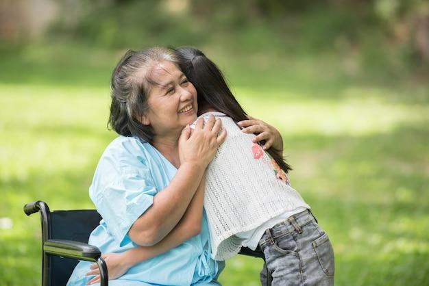Ältere großmutter im rollstuhl mit enkelin im krankenhausgarten
