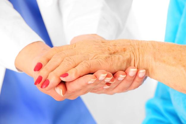 Ältere hände, die vom arzt gehalten werden