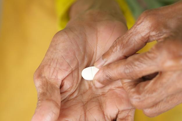 Ältere hand, die pillen mit kopienraum hält