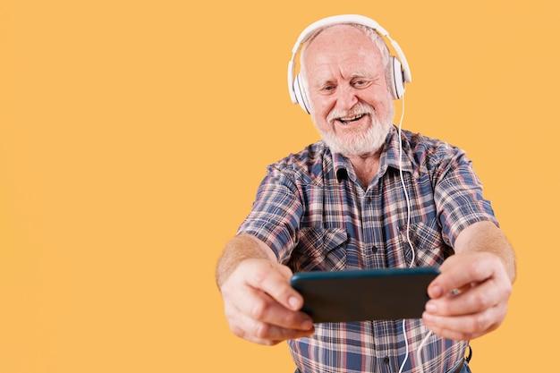 Ältere hörende musik des smiley des niedrigen winkels auf mobile