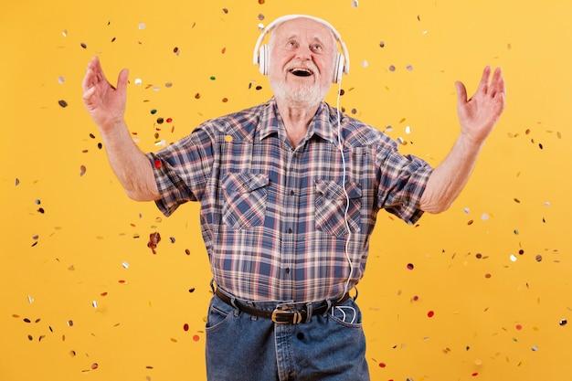 Ältere hörende musik des smiley des niedrigen winkels