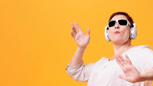 Ältere hörende musik und tanzen der frau des niedrigen winkels
