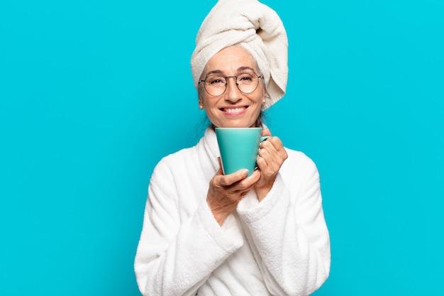 Ältere hübsche frau, die bademantel trägt und einen kaffee hat