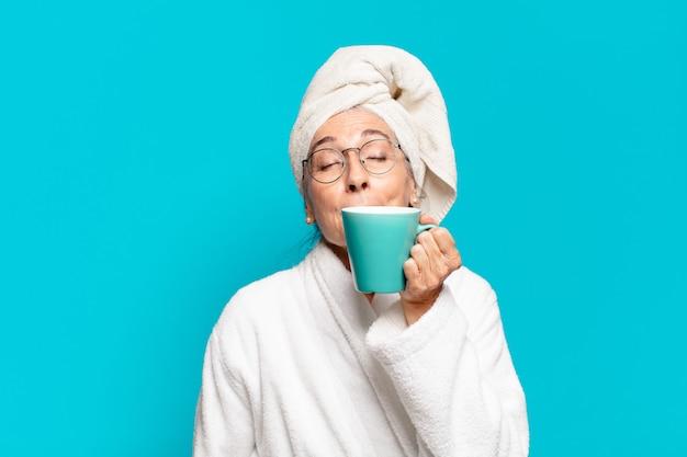 Ältere hübsche frau, die bademantel trägt und einen kaffee trinkt