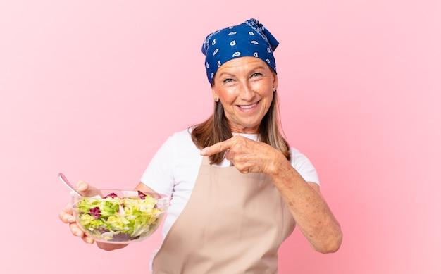 Ältere hübsche frau, die einen salat zubereitet