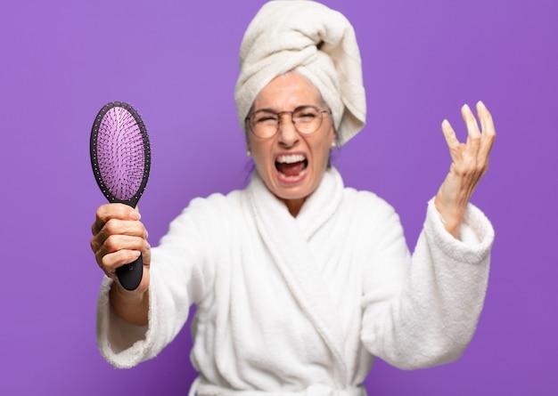 Ältere hübsche frau mit einer haarbürste
