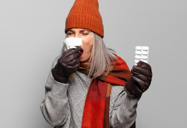 Ältere hübsche frau mit einer pillentablette, die winterkleidung trägt. grippe-konzept