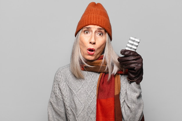 Ältere hübsche frau mit einer pillentablette, die winterkleidung trägt. grippekonzept