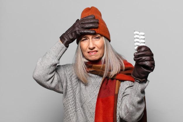 Ältere hübsche frau mit einer pillentablette, die winterkleidung trägt.