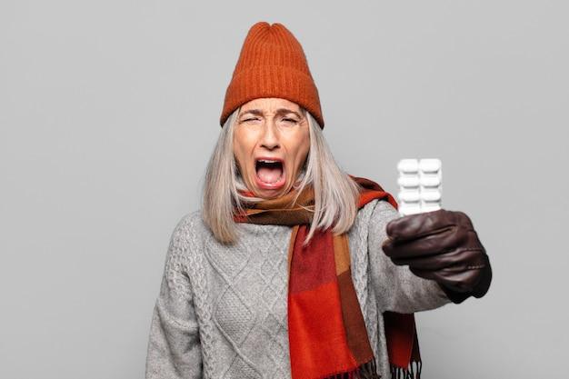 Ältere hübsche frau mit einer pillentablette, die winterkleidung trägt