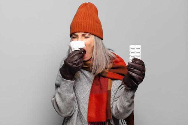 Ältere hübsche frau mit einer pillentablette, die winterkleidungsgrippekonzept trägt