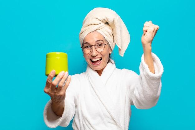 Ältere hübsche frau nach dem tragenden bademantel der dusche. gesichtsreinigungs- oder duschproduktkonzept