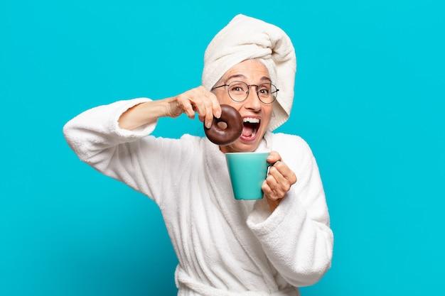 Ältere hübsche frau nach der dusche und im bademantel und beim frühstück mit kaffee und donut