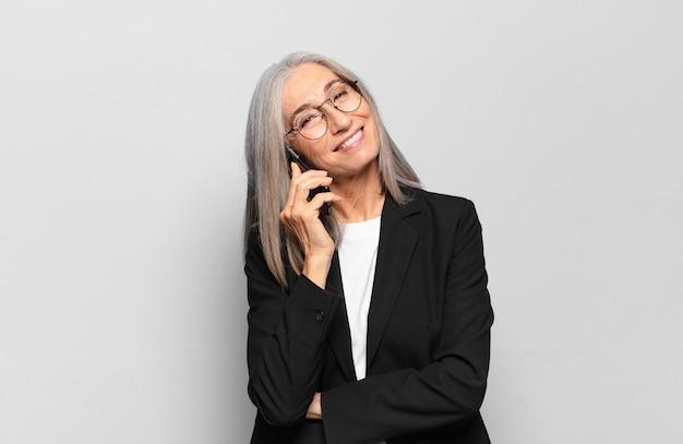 Ältere hübsche geschäftsfrau mit einem intelligenten telefon.