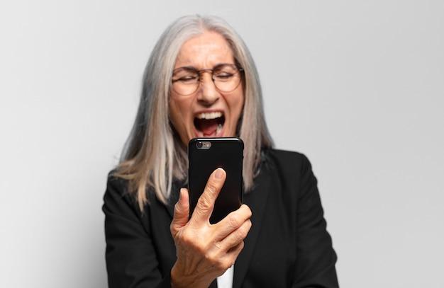 Ältere hübsche geschäftsfrau mit einem smartphone