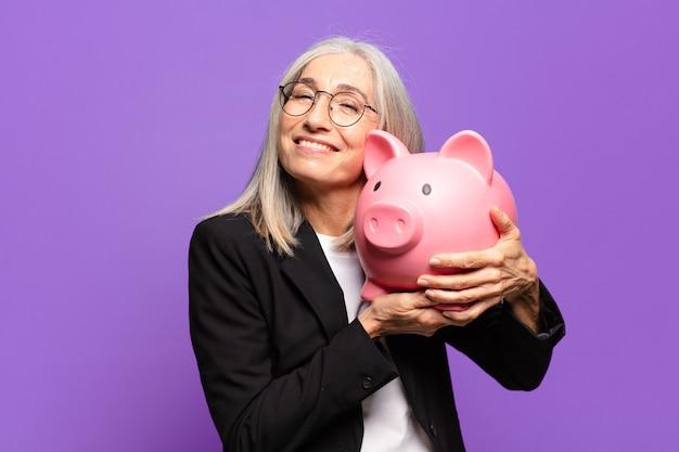 Ältere hübsche geschäftsfrau mit einem sparschwein
