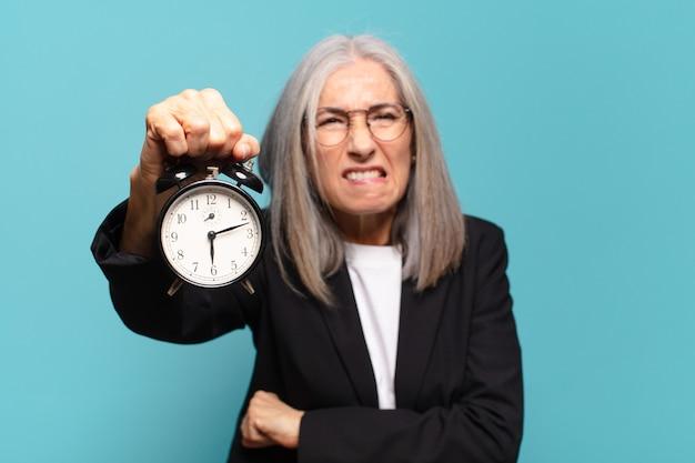 Ältere hübsche geschäftsfrau mit einem wecker. zeitkonzept