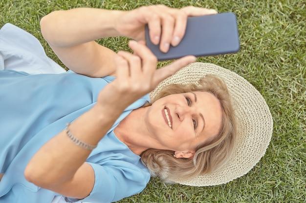 Ältere hübsche kaukasische dame ungefähr 62 jahre alt liegt das gras draußen im hut und mit dem smartphone in ihren händen und lächelt.