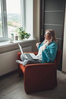 Ältere kaukasische blonde frau benutzt einen laptop, der im sessel sitzt, der etwas nahe dem fenster erklärt, das brille trägt