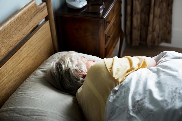 Ältere kaukasische frau, die auf dem bett schläft