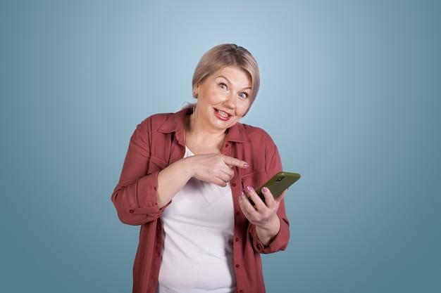 Ältere kaukasische frau, die auf ihr telefon zeigt, das kamera betrachtet und auf einer blauen studiowand aufwirft