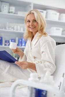Ältere kaukasische frau, die im weißen bademantel lächelt und tee und broschüre im kosmetiksalon hält.