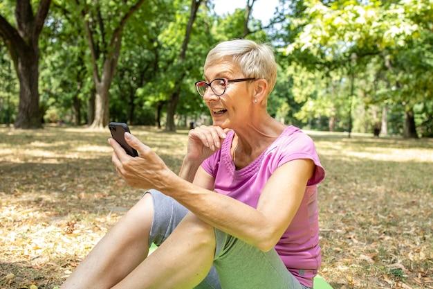 Ältere kaukasische frau, die smartphone-gesundheitsanwendung verwendet und verbrannte kalorien überprüft.