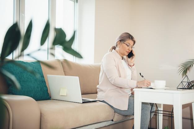Ältere kaukasische frau mit blonden haaren und brillen, die von zu hause am pc arbeiten, während sie etwas schreiben