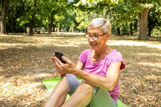 Ältere kaukasische frau mit smartphone-gesundheitsanwendung für das training in der natur.