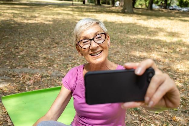 Ältere kaukasische frau mit smartphone und selfie nach dem training.