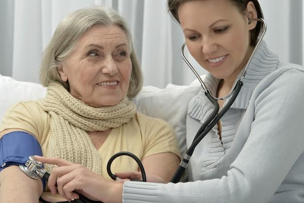 Ältere kranke frau mit fürsorglicher tochter, die den blutdruck misst