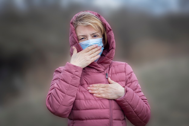 Ältere kranke kranke ernste frau in der medizinischen sterilen maske auf ihrem gesicht, das hustet und hand auf ihrer brust, lunge ,. pandemie, virus, covid-19-konzept. coronavirus symptome