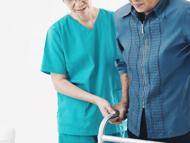 Ältere krankenschwester hilfe ältere frau mit walker.
