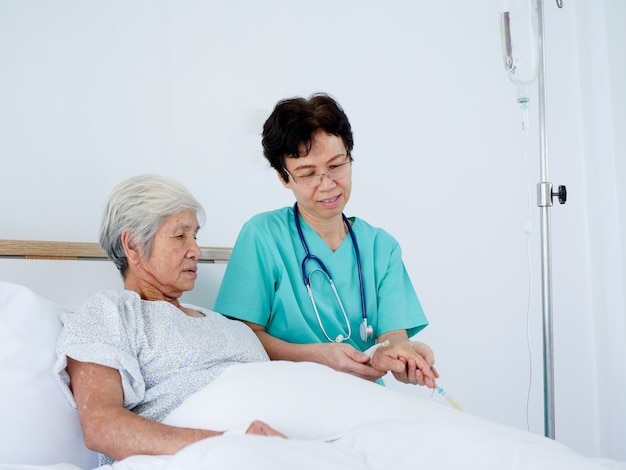 Ältere krankenschwester mach's gut ältere frau, die in krankenhausbett legt.