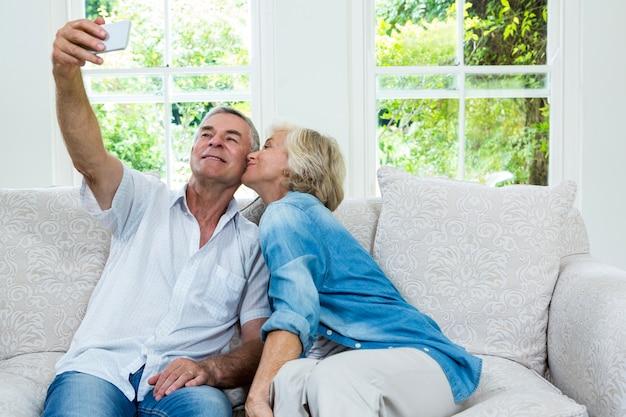Ältere küssende frau während mann, der selfie im wohnzimmer nimmt