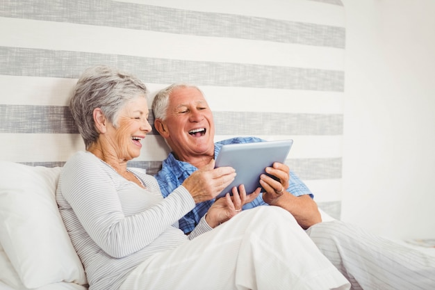 Ältere lachende paare bei der anwendung der digitalen tablette im schlafzimmer