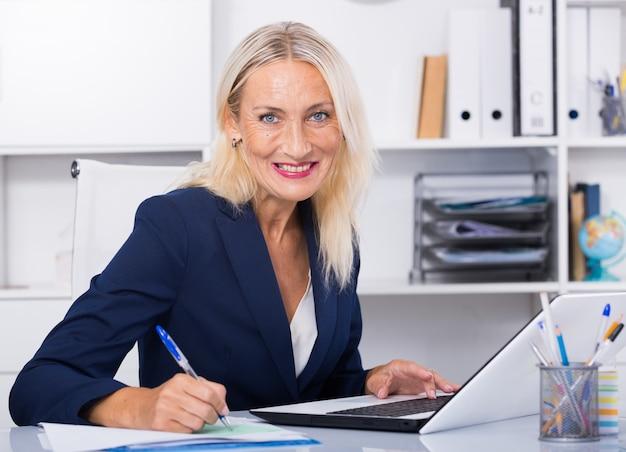 Ältere lächelnd geschäftsfrau arbeiten im büro