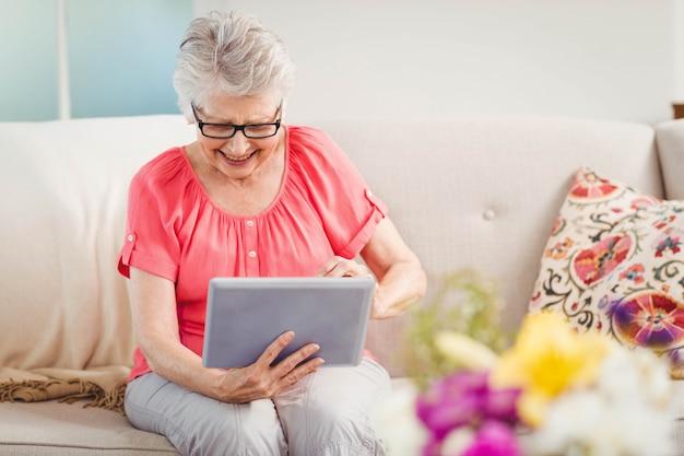 Ältere lächelnde frau bei der anwendung der digitalen tablette zu hause