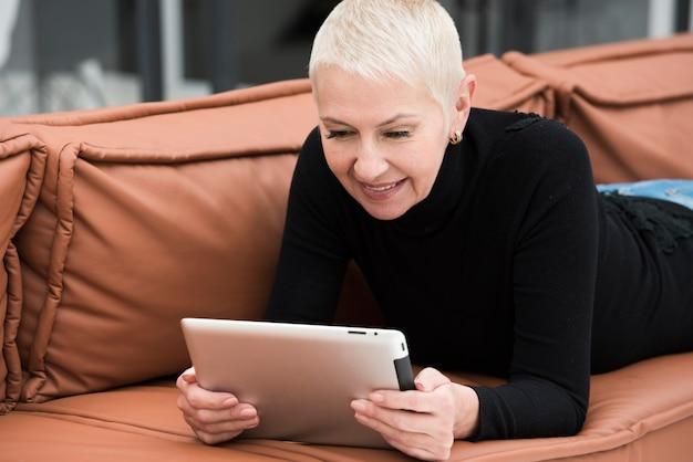 Ältere lächelnde frau beim betrachten der tablette auf sofa