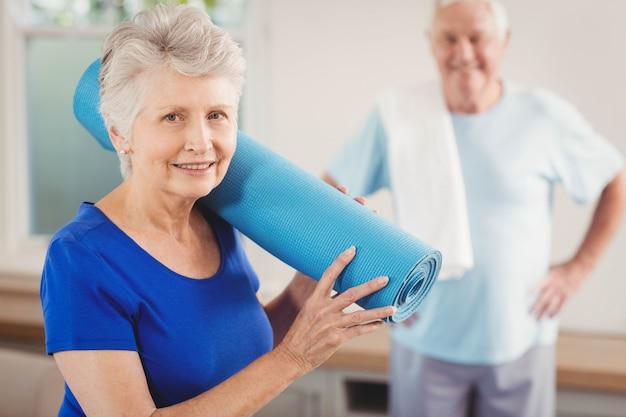 Ältere lächelnde frau beim oben packen nach training
