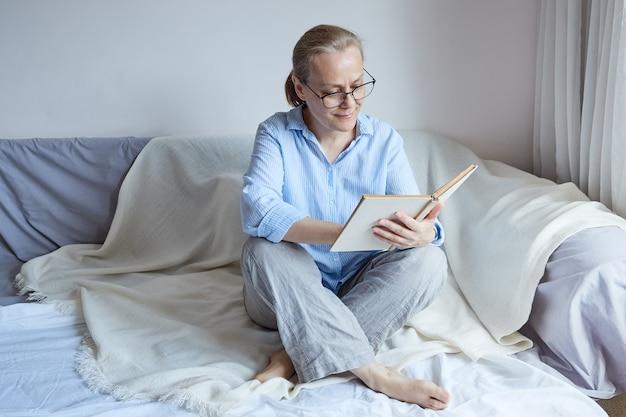 Ältere lächelnde frau mit brille sitzt mit ihren beinen auf dem sofa, liest ein buch.