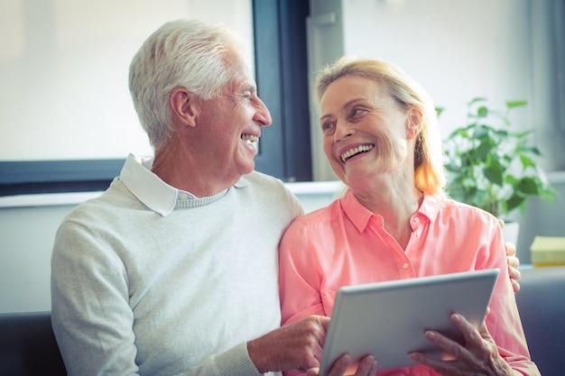 Ältere lächelnde paare bei der anwendung der digitalen tablette