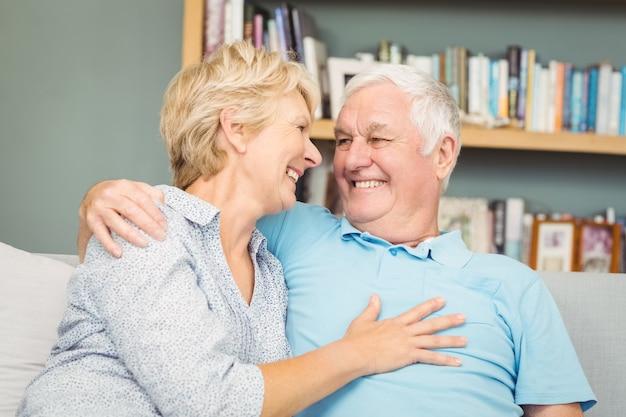 Ältere lächelnde paare beim umarmen auf sofa