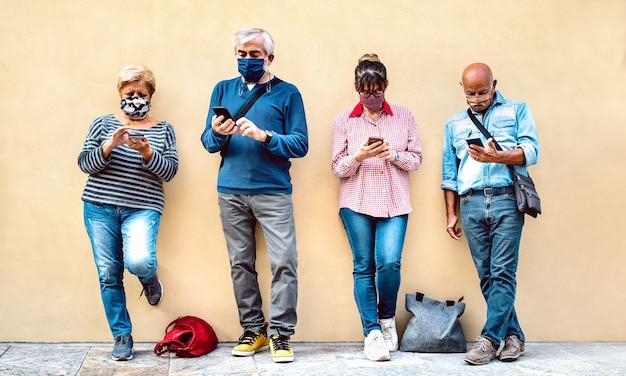 Ältere leute, die mobiles smartphone mit abgedeckter gesichtsmaske verwenden