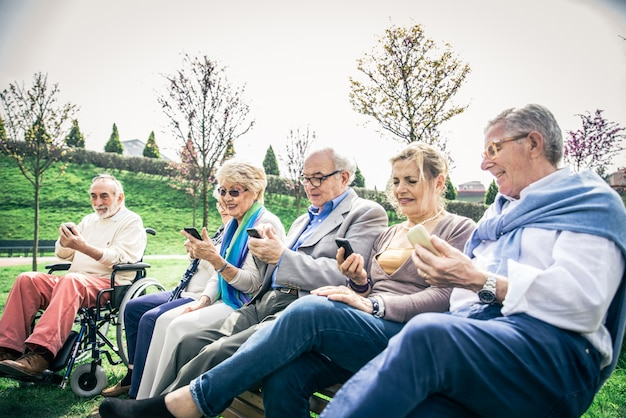 Ältere leute, die smartphones schauen