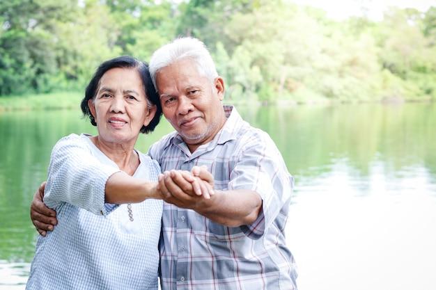 Ältere liebhaber, die händchen haltend im garten tanzen viel spaß im ruhestand. konzepte für seniorengemeinschaften
