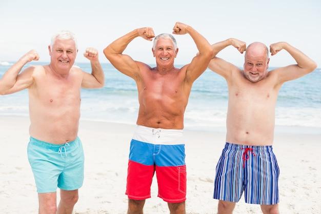 Ältere männer, die mit ihren muskeln aufwerfen